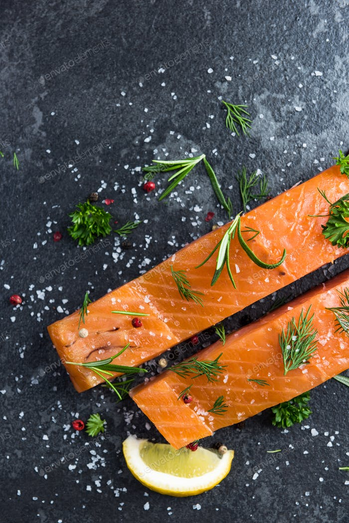Salmon fillers with salt on dark marble