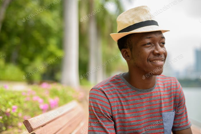 Young handsome African man smiling and thinking in park