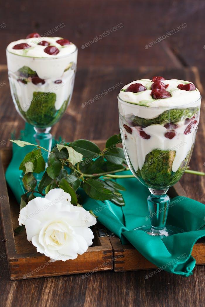 Tiramisu in a glass of tea match and cherry.