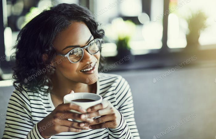 Young African woman sitting in a cafe enjoying some coffee