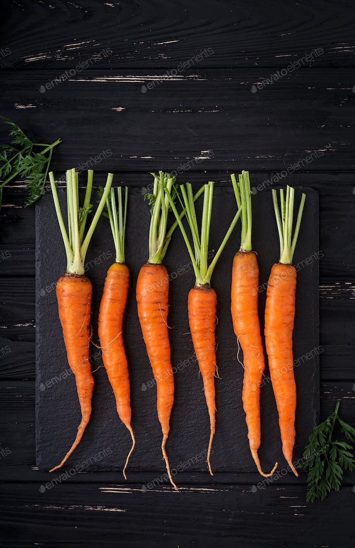 Bunch of fresh carrots with green leaves on  dark  wooden background. Flat lay. Top view