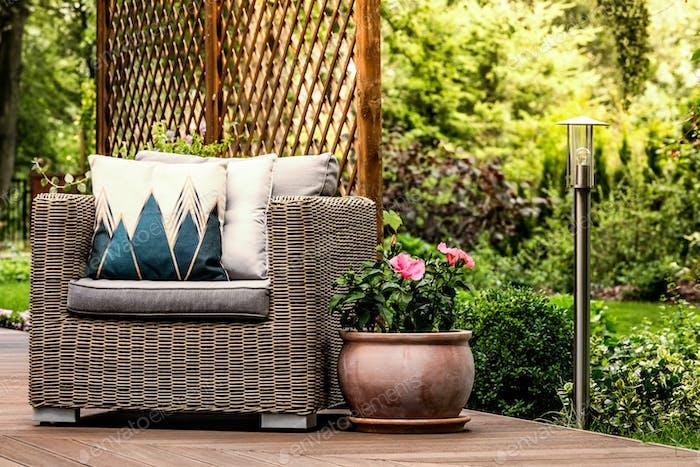 Rattan armchair on wooden terrace
