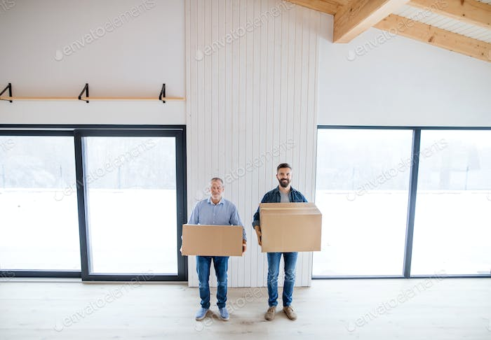 Two men holding cardboard boxes in front of them when furnishing new house.