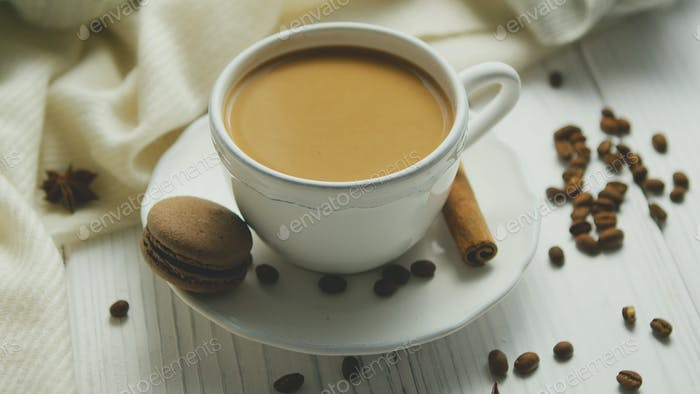 Cup of coffee with cookie and cinnamon