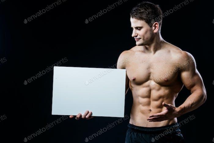 Ganzkörper-Bodybuilder mit weißem, weißen Plakat isoliert auf schwarzem Hintergrund. Schöner muskulöser Mann