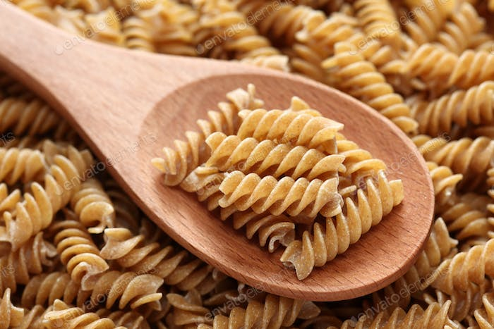 Raw brown pasta on a wooden spoon