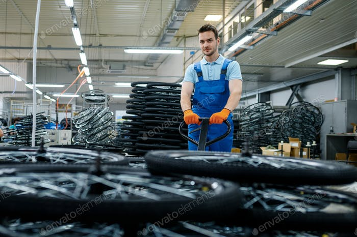 Worker carries bicycle wheels on a cart, factory