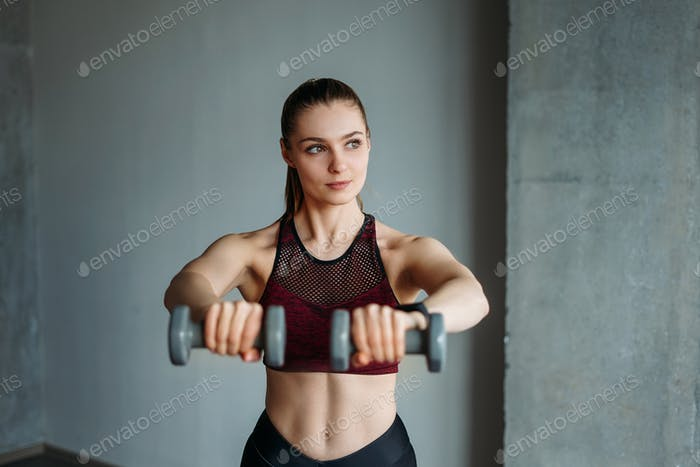 Young woman in sport wear smiling girl trains with dumbbells