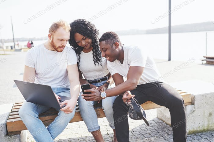 Beautiful multi ethnic friends using a laptop in the Street. Youth lifestyle concept