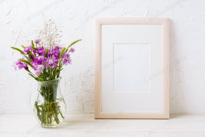 Wooden frame mockup with purple burdocks in jug