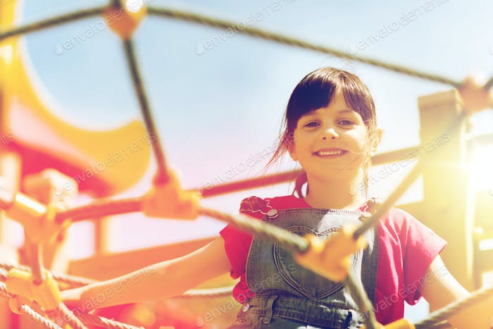 happy little girl climbing on children playground