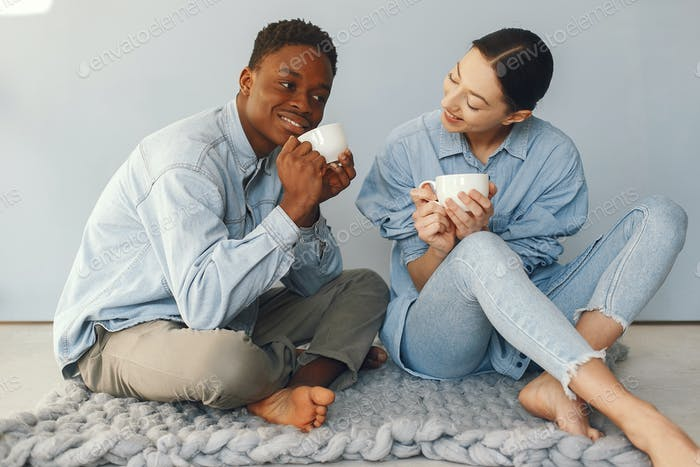 International couple drinking a coffee on a blue background