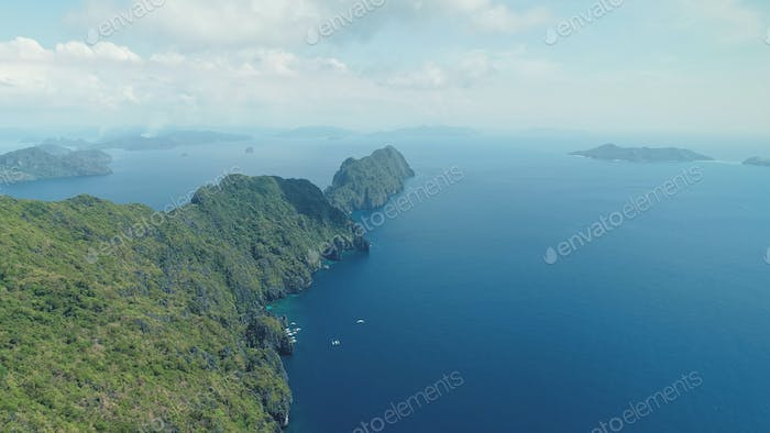 Amazing seascape of sea bay with rocks beach. Mountain island with green tropic forest at hill shore