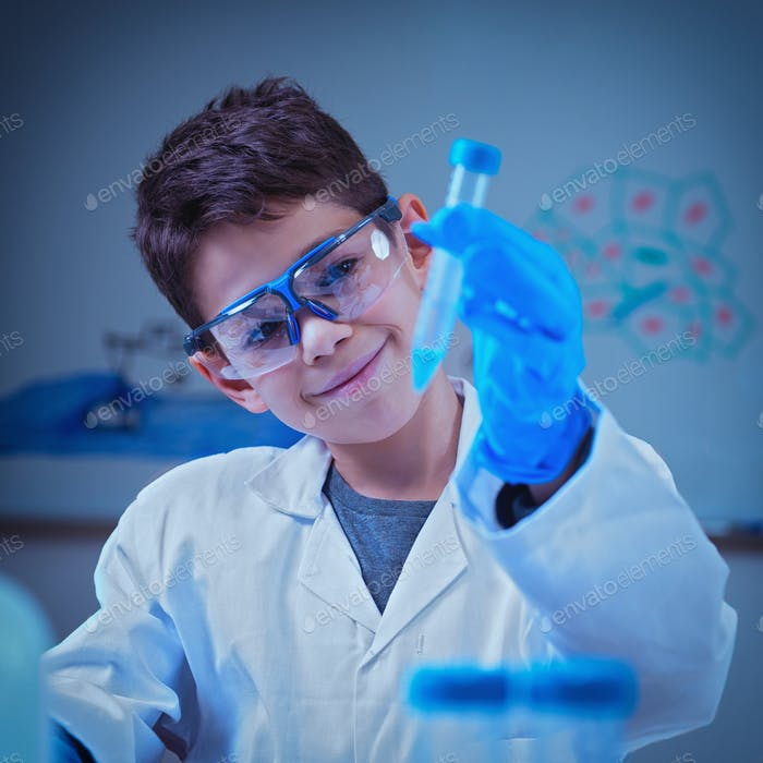 Boy in lab coat holding test tube