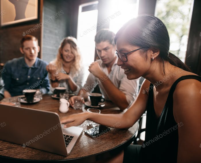 Group of friends in cafe watching something online on laptop