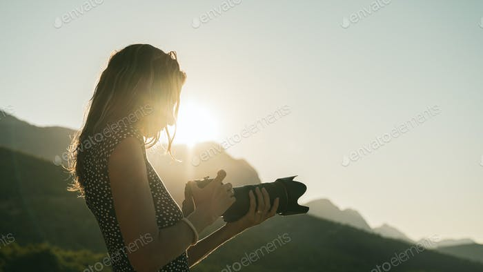 Young female photographer looking at her dslr camera