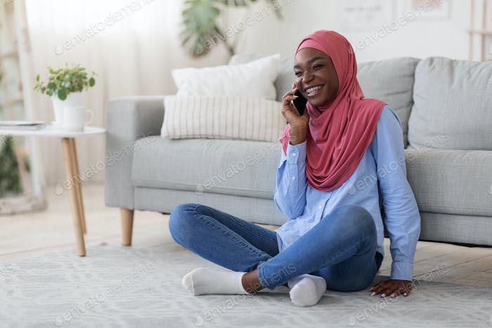 Joyful black islamic lady talking on cellphone, relaxing on floor at home