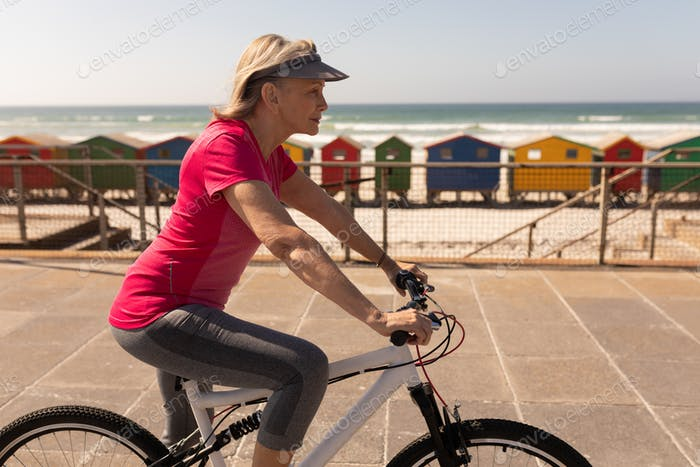 Side view of senior woman riding a bicycle on a promenade at beach