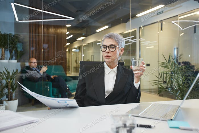 Successful Female Boss Working in Glass Office