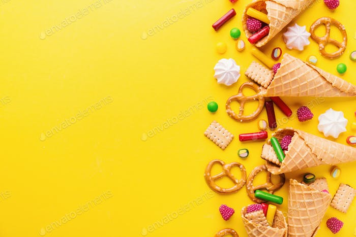 Funny tasty sweets on yellow background