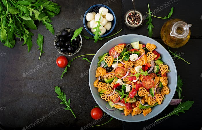 Pasta in the shape heart salad with tomatoes, cucumbers, olives, mozzarella