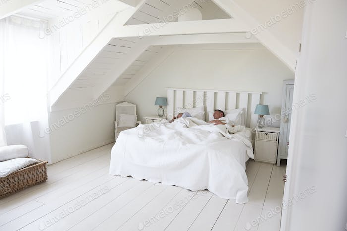 Couple Sleeping In Light And Airy White Bedroom