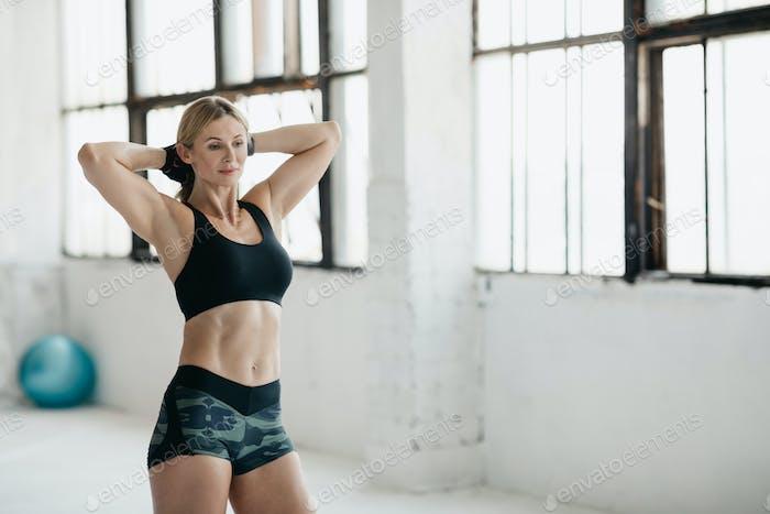 Demonstriert Bizeps und schlanken Körper im mittleren Alter. Schöne Frau in Sportbekleidung gefaltete Arme hinter