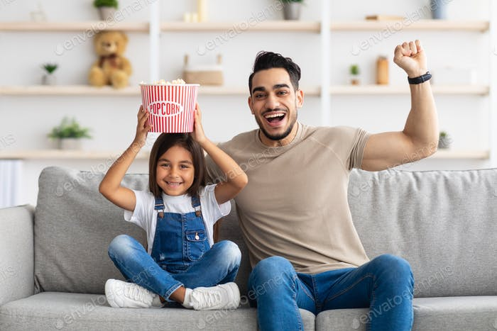 Happy young family watching television sitting on couch