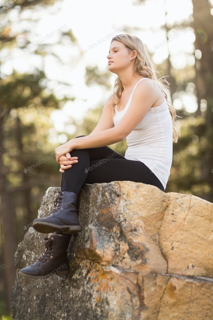 Young jogger sitting on a rock and looking away in the nature