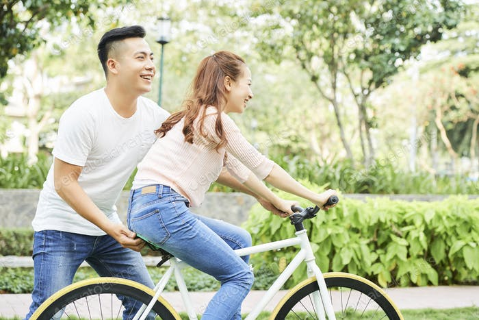 Couple learning to ride on bicycle