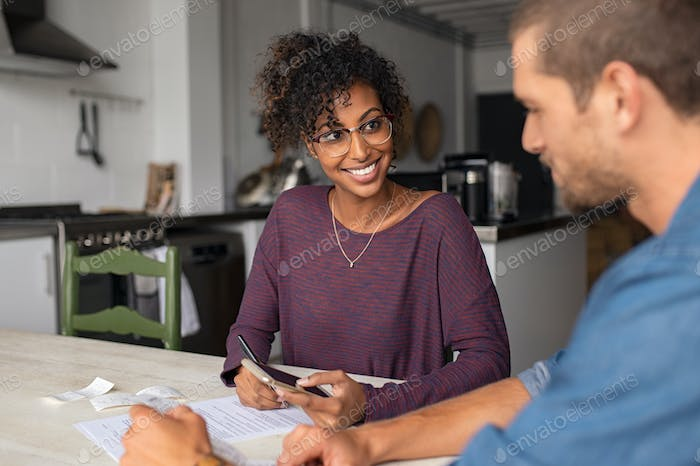 Young smiling couple managing expenses
