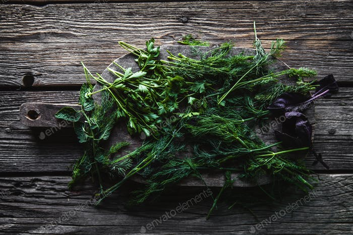 Parsley and dill on a cutting board, wooden background