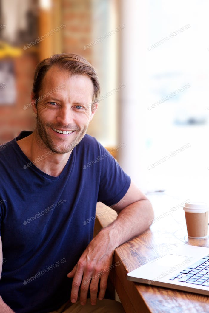 handsome man smiling with laptop at cafe