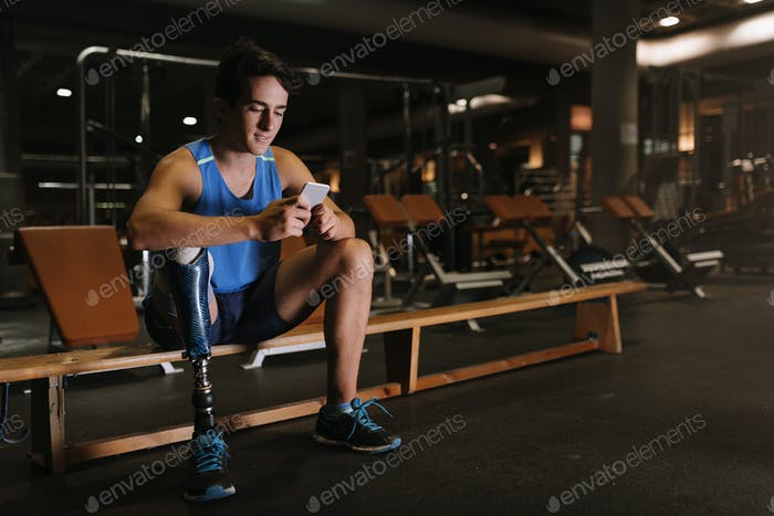 Disabled young man using his mobile in the gym.