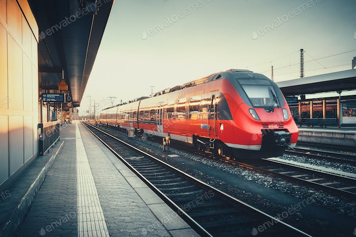 Beautiful railway station with modern red commuter train at suns
