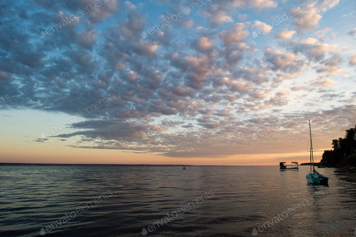 small fishing boat on beach with sunset background in the morning
