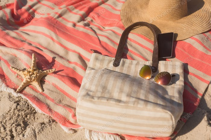 Close-up of mobile phone and accessories on picnic blanket at beach on a sunny day