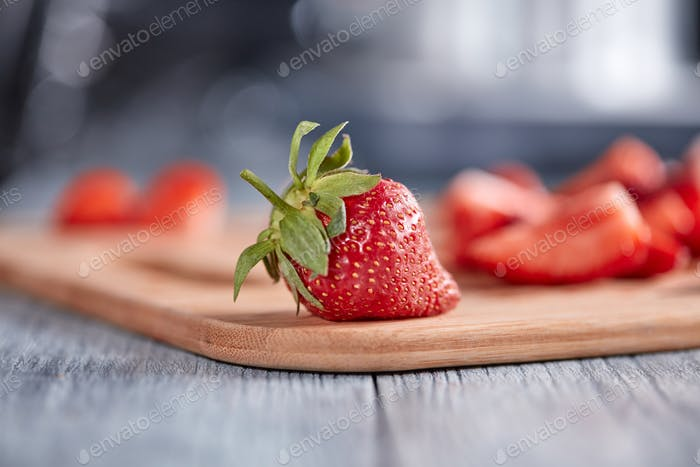 On the kitchen board juicy organic strawberries with green leaves on a wooden table. Healthy berry