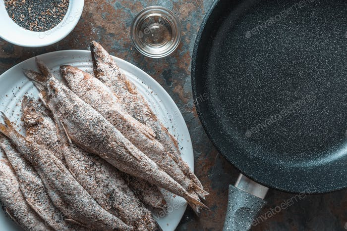 Smelt on a plate, frying pan, salt and spices close-up