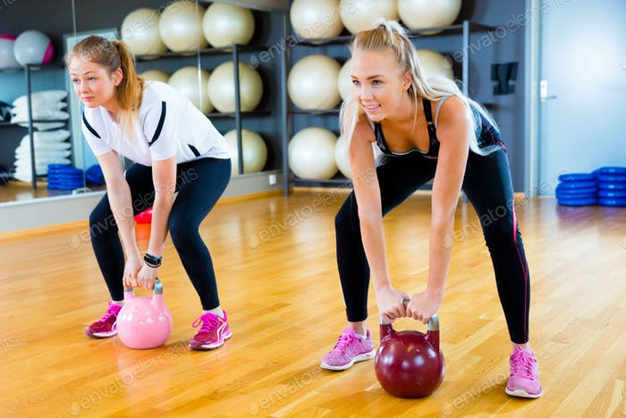 Determined Friends Lifting Kettlebells In Fitness Center