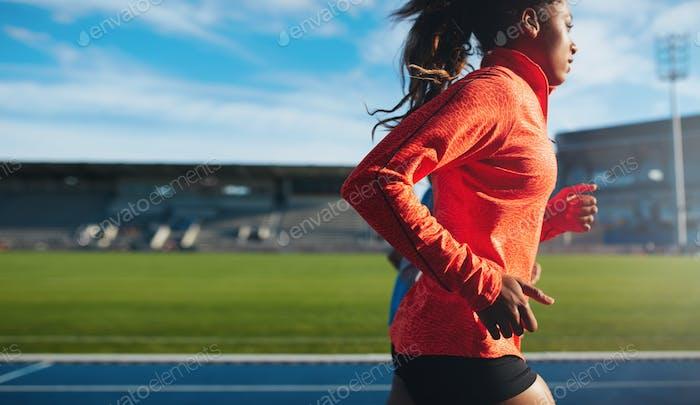African female athlete training on race track