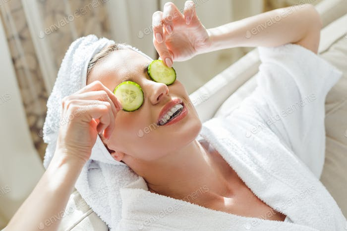 woman relaxing with cucumber slices on eyes