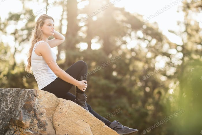 Young jogger sitting on rock and looking away in the nature