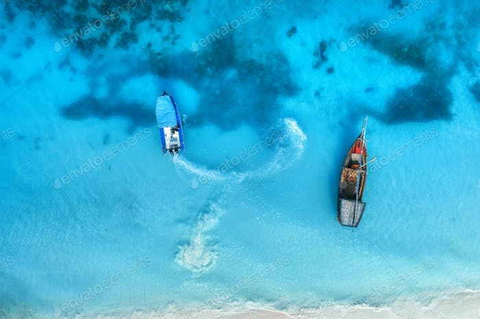 Aerial view of the fishing boats in clear blue water at sunset
