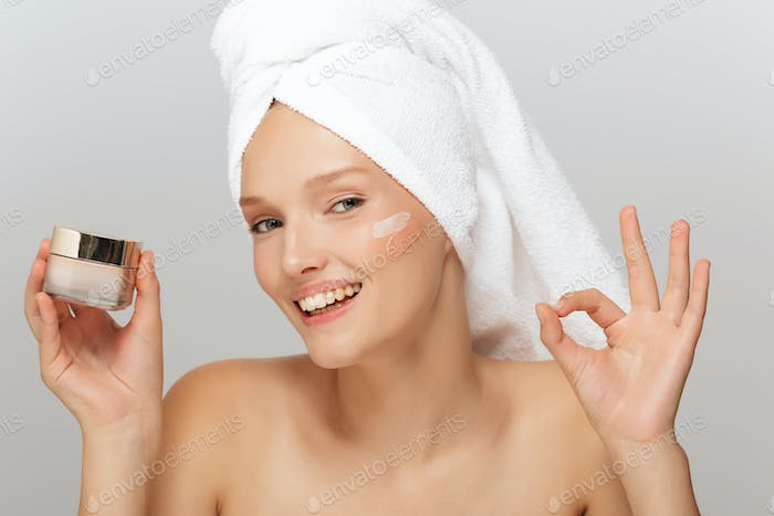Portrait of young pretty smiling lady with white towel on head w
