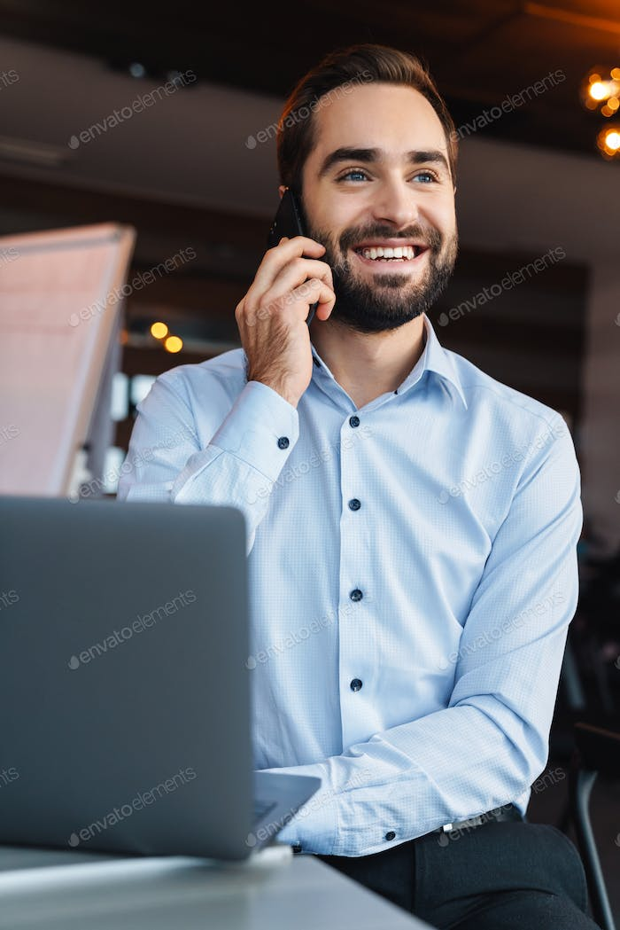 Portrait of businessman talking on cellphone while working in office