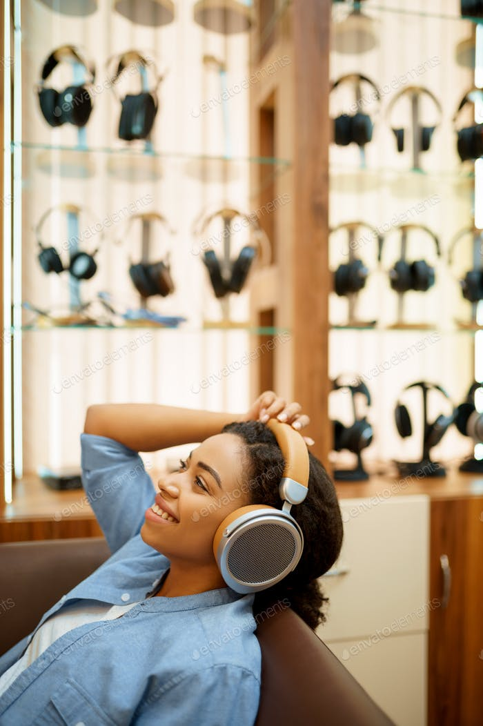 Happy woman listening to music, headphones store