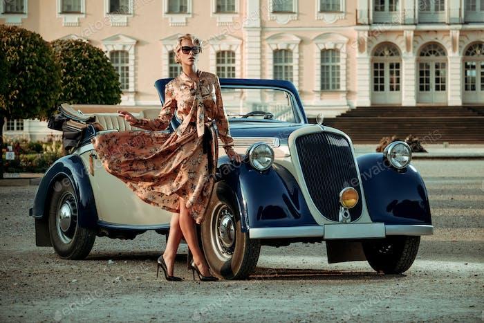 Schöne Dame mit Tasche in der Nähe klassischer Cabrio