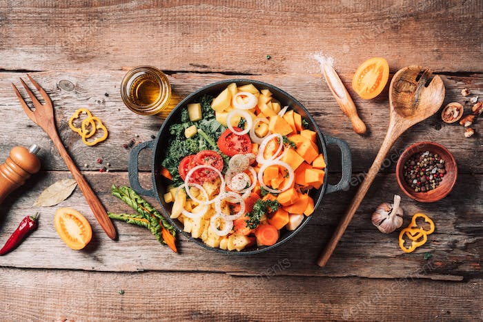 Big pot with sliced colorful vegetables and cooking utensils on rustic wooden background. Top view