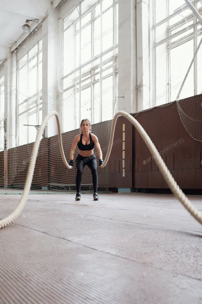 woman in black sportswear burning calories by doing exercise with ropes in gym